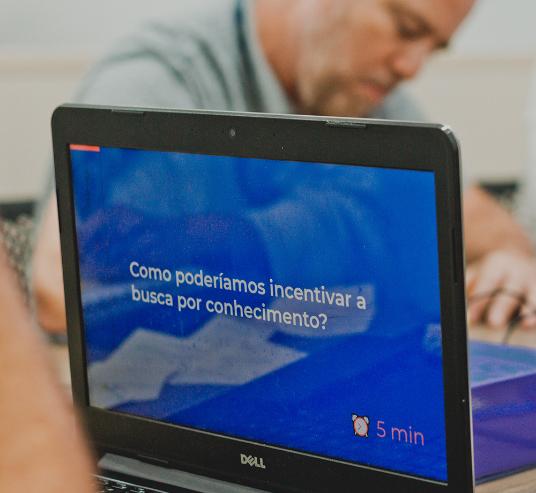 Foto de notebook com a frase 'Como poderíamos incentivar a busca por conhecimento?'
